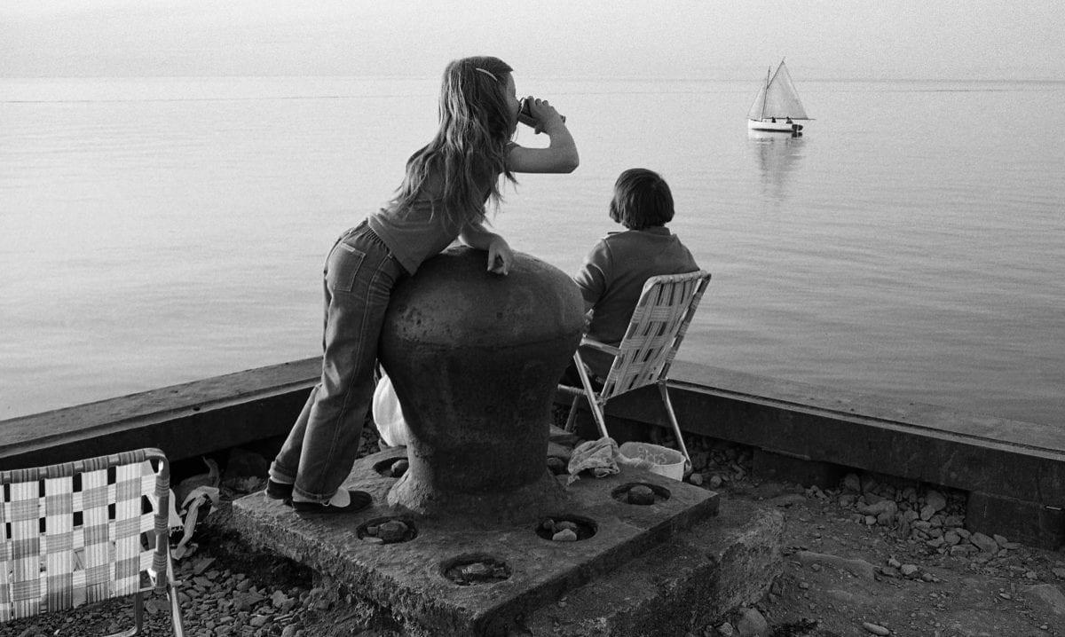 Deux enfant regardent une mer un petit voilier sur une mer paisible